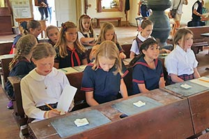 Sitting at desks in pioneer era schoolhouse on a field trip.
