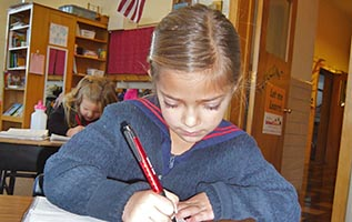 Young girl practices writing with a pen on National Pen Day.