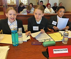 Participating as prosecuting attorneys in a Mock Trial.