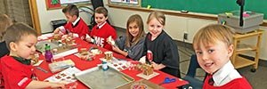 Elementary students decorate gingerbread houses for the holidays.